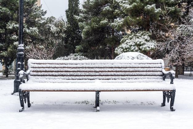 Banco no parque da cidade coberto de neve