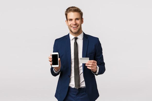 Banco on-line, finanças e conceito de negócio. bem sucedido empresário caucasiano bonito terno clássico, promover o sistema bancário, mostrando a tela do smartphone e cartão de crédito, sorrindo
