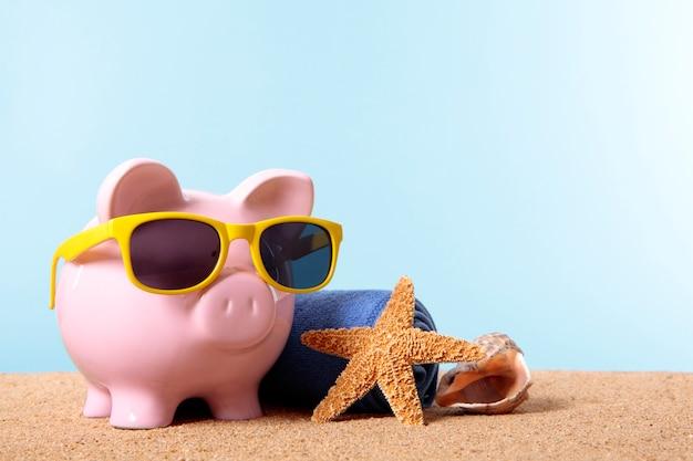 Banco piggy em uma praia com óculos de sol