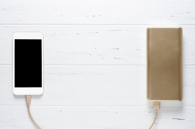 Banco portátil do poder e smartphone na madeira branca