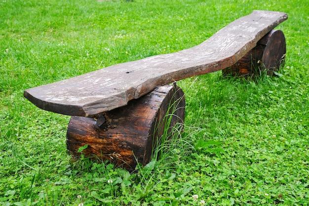 Banco velho de madeira em um fundo de grama verde