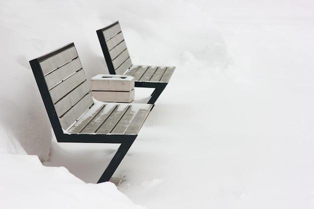 Bancos da cidade em um fundo branco coberto de neve