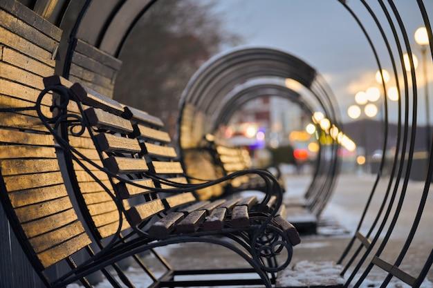 Bancos de madeira à luz da lanterna no parque da cidade. pessoas passando por um beco. paisagem de inverno à noite.