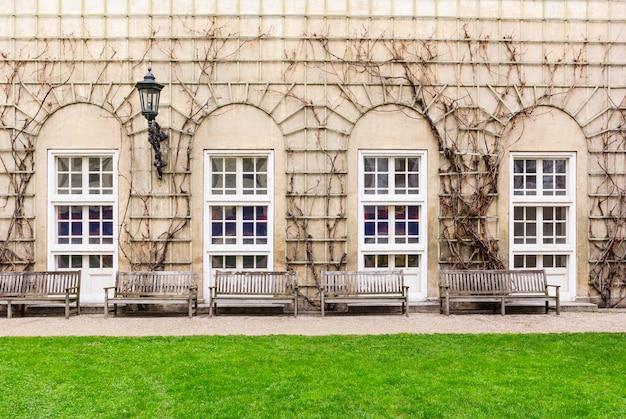 Bancos de madeira de frente para a parede com os vitrais arqueados