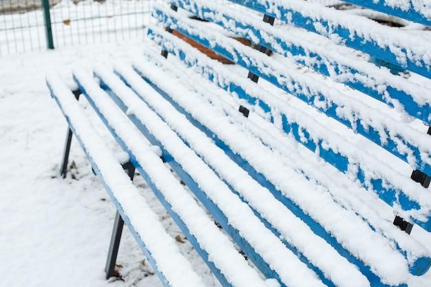 Bancos para descanso são cobertos de neve no parque no inverno