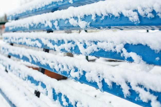Bancos para descanso são cobertos de neve no parque no inverno.