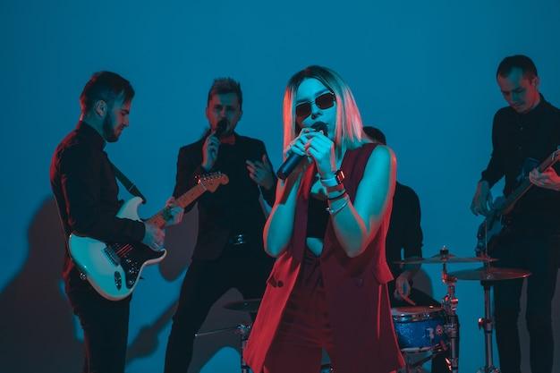 Banda de jovens músicos caucasianos se apresentando em luz de néon no fundo azul do estúdio