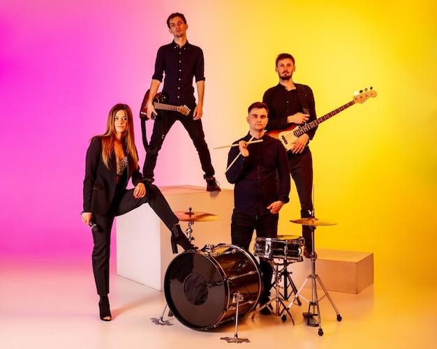 Banda de jovens músicos caucasianos se apresentando em luz de néon no fundo gradiente do estúdio