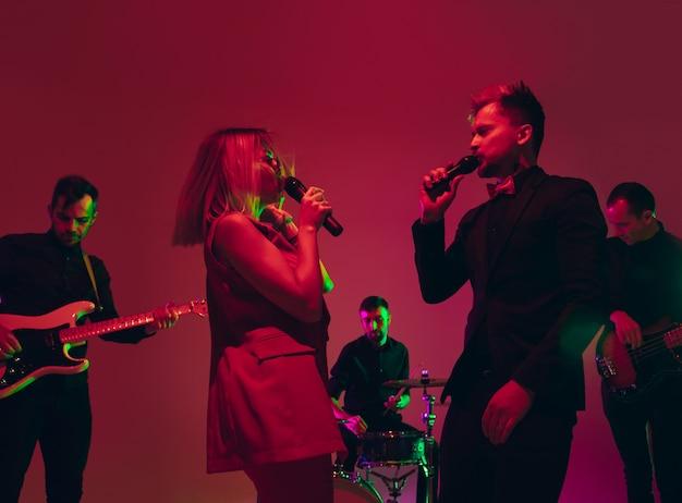 Banda de jovens músicos caucasianos se apresentando em luz de néon no fundo vermelho do estúdio