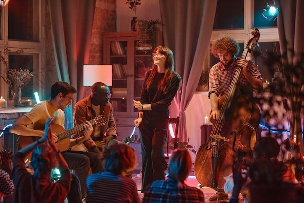Banda de música com cantor mostrando sua performance para as pessoas na boate