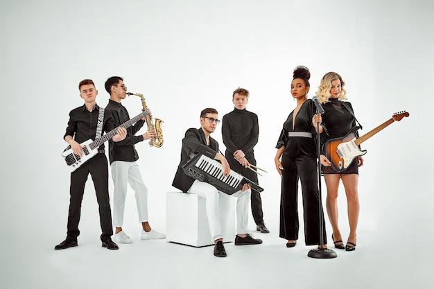 Banda de música multirracial em um fundo branco. um grupo de músicos internacionais ensaiando uma apresentação de concerto. vocalista, ram, guitarrista.
