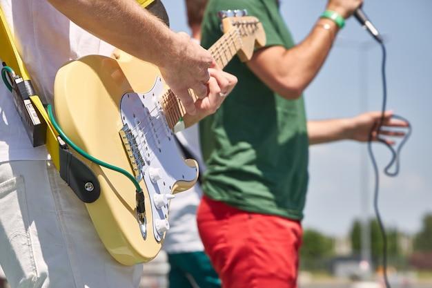 Banda de rock jovem executa suas músicas na rua, close-up