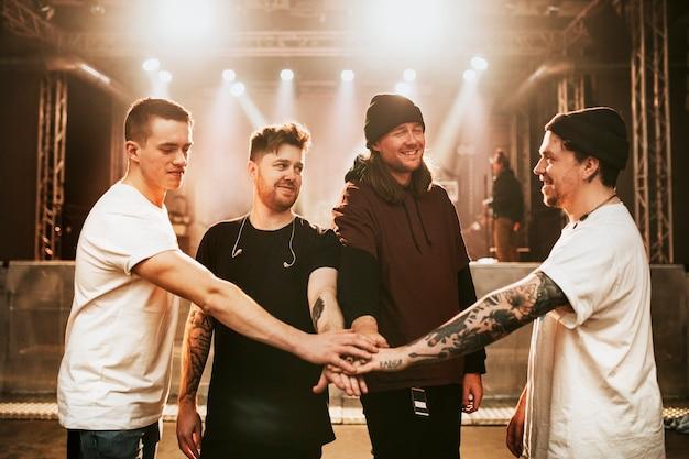 Banda feliz dando as mãos antes de um show