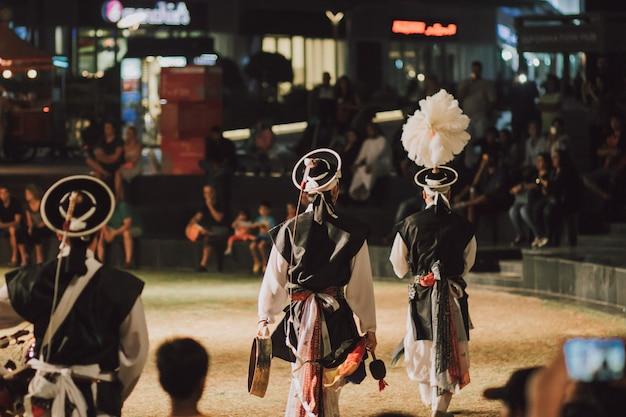 Banda folclórica coreana tocando com instrumento tradicional ao ar livre
