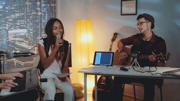 Banda moderna ensaiando no estúdio em casa: jovem tocando guitarra e garota de raça mista cantando no microfone