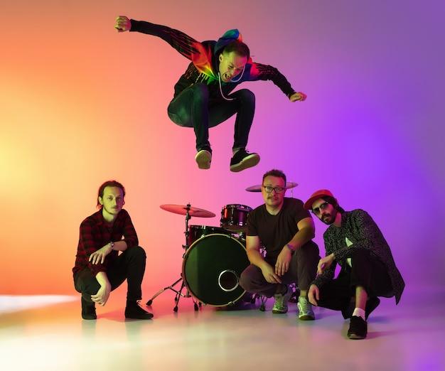 Banda musical masculina tocando luz de néon Foto Premium