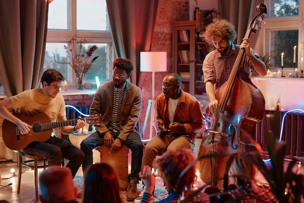 Banda musical tocando diferentes instrumentos musicais e cantando enquanto se apresenta para as pessoas no clube