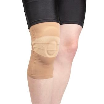 Bandagem para fixar o joelho ferido da perna humana em um tecido branco