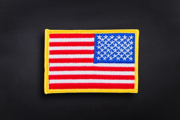 Bandeira americana bordada contra o fundo do quadro negro
