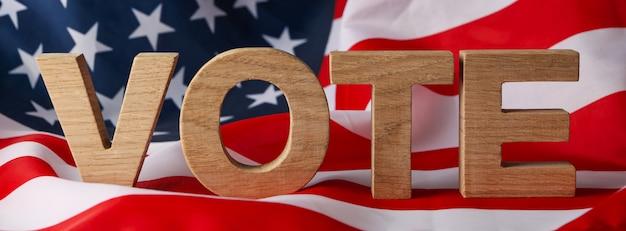Bandeira americana com a palavra voto feita de letras de madeira