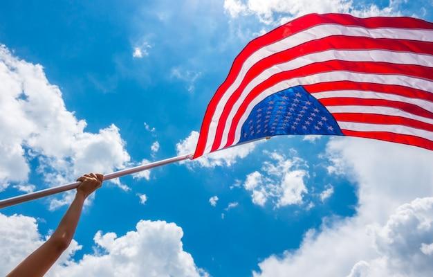 Bandeira americana com estrelas e listras segurar com as mãos contra blu