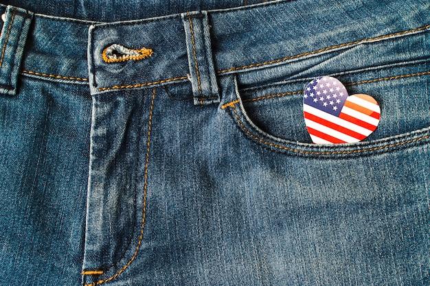 Bandeira americana da forma do coração no bolso das calças de brim da sarja de nimes
