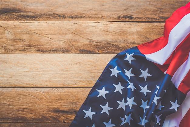 Bandeira americana, deitado sobre um piso de madeira.
