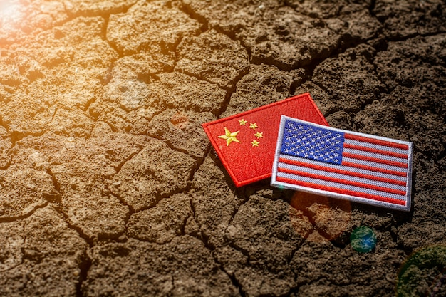 Bandeira americana e bandeira da china em terreno rachado abandonado.