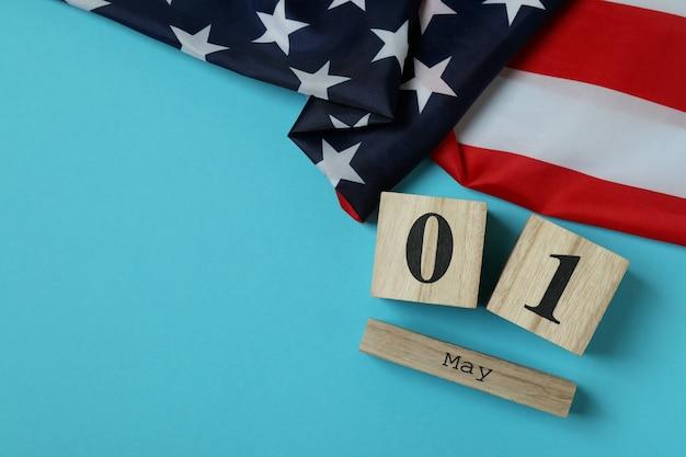 Bandeira americana e calendário de madeira com 1 de maio em azul