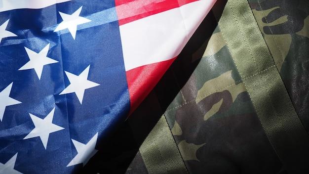 Bandeira americana e chapéu ou bolsa militar. ângulo de visão superior. chapéu de soldado ou capacete com a bandeira nacional americana em fundo preto. representa o conceito militar por objeto de camuflagem e a bandeira da nação dos eua.