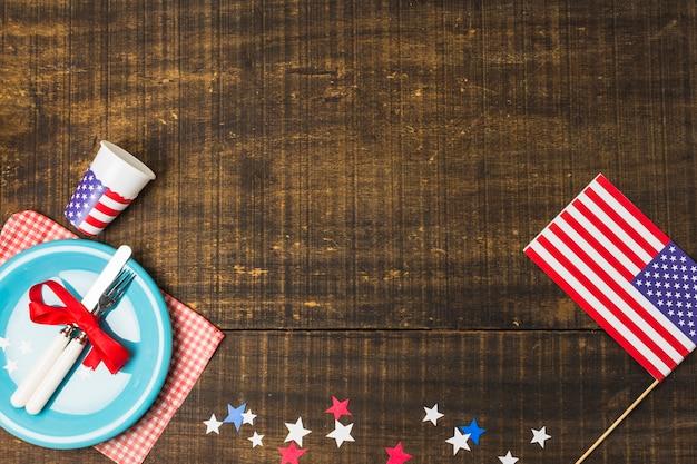 Bandeira americana e estrelas de feltro decoram a mesa com um prato azul na mesa de madeira