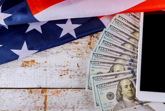 Bandeira americana e notas de 100 notas de dólar dos eua em um tablet digital