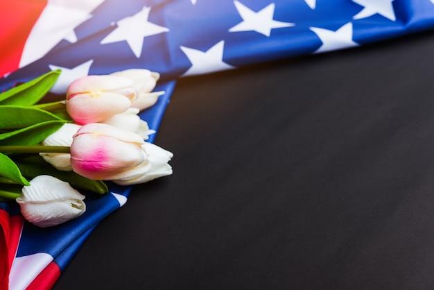 Bandeira americana e uma flor de tulipa em um preto
