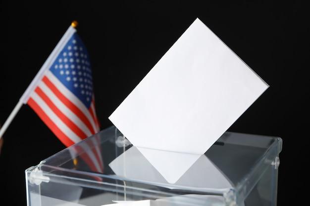 Bandeira americana e urna de votação com cédula na superfície preta