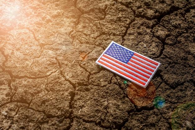 Bandeira americana em solo rachado abandonado.
