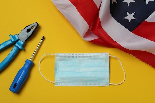 Bandeira americana, máscara e ferramentas em fundo amarelo