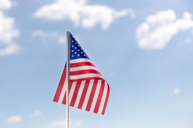 Bandeira americana no céu azul com nuvens