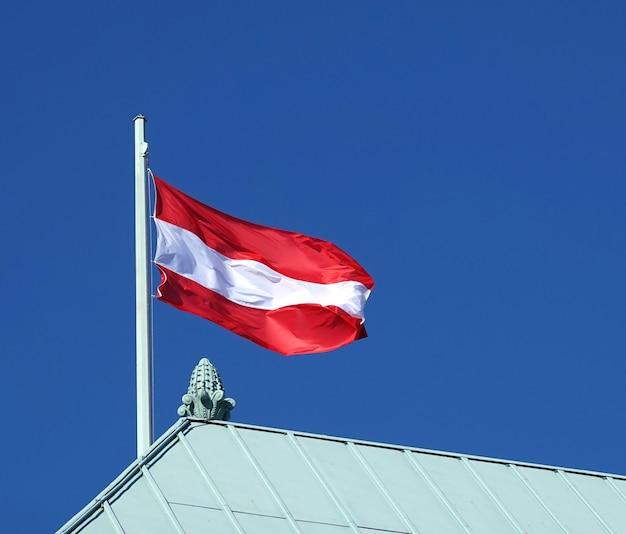 Bandeira austríaca no topo do telhado da casa em dia ensolarado e sem nuvens no céu azul