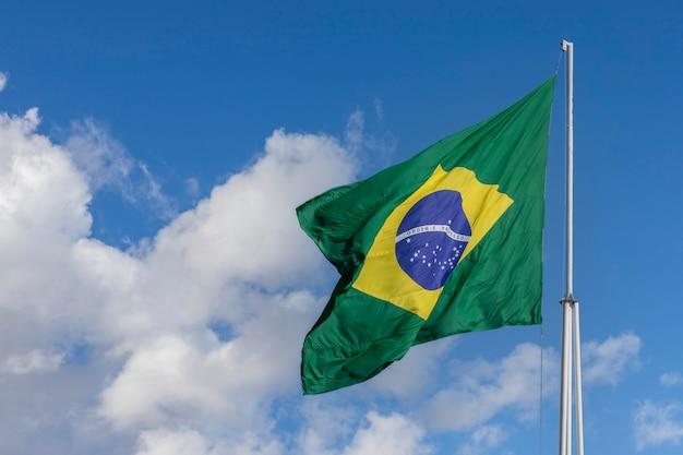 Bandeira brasileira tremulando no céu azul com nuvens. bandeira do brasil