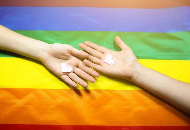 Bandeira colorida da comunidade lgbt. duas mãos de mulheres no fundo do arco-íris. problemas com lésbicas e gays. legalização do casamento para casais com orientação homossexual.