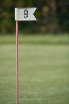 Bandeira com o número 9 utilizada na prática do golfe para marcar o buraco do número correspondente