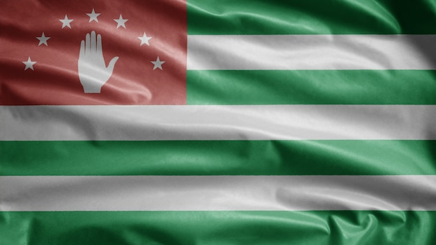 Bandeira da abecásia balançando ao vento. perto da bandeira da abkházia soprando, seda macia e suave. fundo de estandarte de textura de tecido de pano