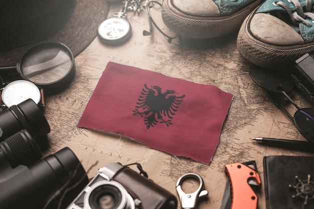 Bandeira da albânia entre acessórios do viajante no antigo mapa vintage. conceito de destino turístico.