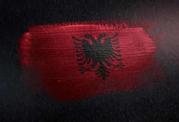 Bandeira da albânia feita de tinta de pincel metálico na parede escura de grunge