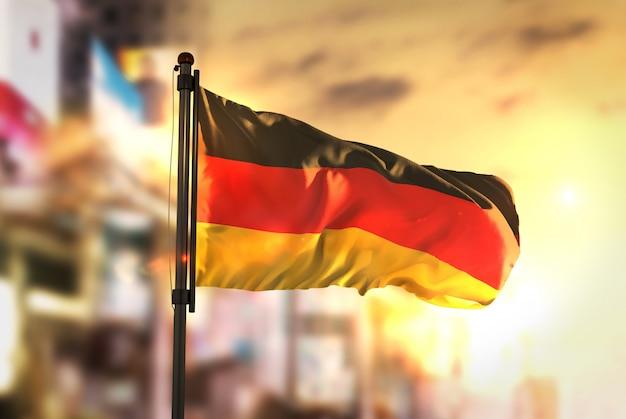 Bandeira da alemanha contra a cidade fundo borrado no amanhecer luz de fundo
