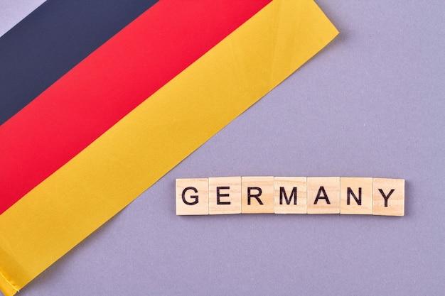 Bandeira da alemanha em fundo roxo. conceito de país escrito com blocos de madeira.