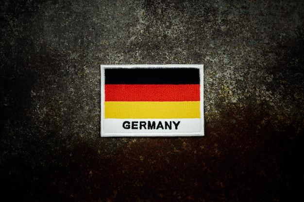 Bandeira da alemanha no chão de metal abandonado enferrujado no escuro.