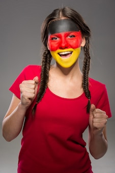 Bandeira da alemanha pintado em um rosto de uma jovem mulher.