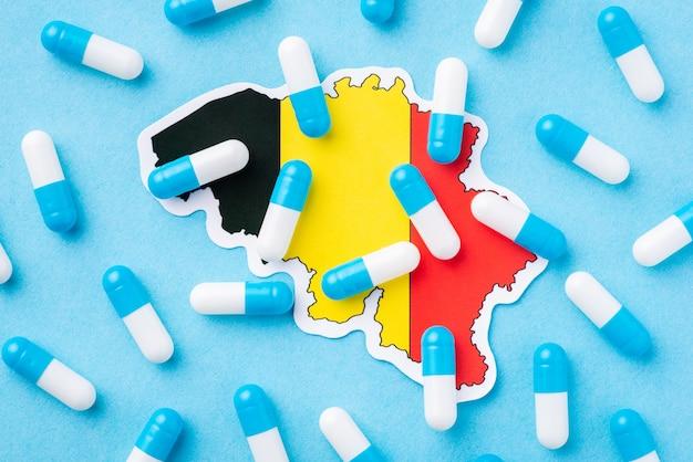 Bandeira da bélgica e pílulas cápsulas azuis e brancas no topo