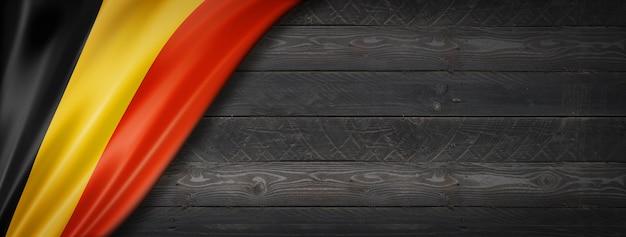 Bandeira da bélgica na parede de madeira preta. banner panorâmico horizontal.